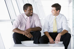 Dos hombres de negocios que se sientan en hablar del pasillo de la oficina Imágenes de archivo libres de regalías