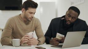 Dos hombres de negocios que se sientan en la cocina abierta con el dinero en manos almacen de video