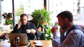 Dos hombres de negocios que se sientan en la tabla del café, usando el ordenador portátil, y hablando por el teléfono elegante almacen de metraje de vídeo