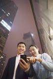 Dos hombres de negocios que sonríen y que miran el teléfono, señalando, al aire libre en la noche, la opinión de ángulo bajo fotografía de archivo libre de regalías