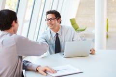 Dos hombres de negocios que tienen reunión alrededor del vector en oficina moderna Fotografía de archivo libre de regalías