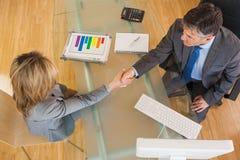Dos hombres de negocios que tienen un apretón de manos sobre un escritorio Imagenes de archivo