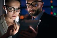 Dos hombres de negocios que trabajan en la tableta en la noche fotos de archivo