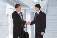 Dos hombres de negocios saludan en collage del centro de asunto Imagenes de archivo