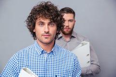 Dos hombres de negocios serios que sostienen carpetas Fotografía de archivo libre de regalías