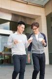 Dos hombres de negocios sonrientes que caminan y que hablan en la ciudad Fotos de archivo libres de regalías