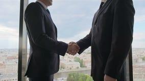 Dos hombres de negocios sonrientes que sacuden las manos