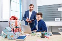 Dos hombres de oficinistas sonríen, al lado de las cajas de regalo de la Navidad imagen de archivo