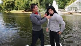 Dos hombres divertidos jovenes en músculo falso rellenaron los trajes carismáticamente bailan en barco almacen de video