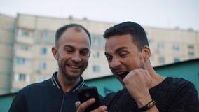 Dos hombres emocionalmente felices después de las noticias en el teléfono almacen de metraje de vídeo