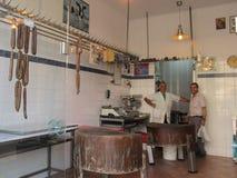 Dos hombres, empleados de la tienda de carne que sonríen mirando la cámara Grecia, Kavala - Sertember 10, 2014 imagen de archivo libre de regalías
