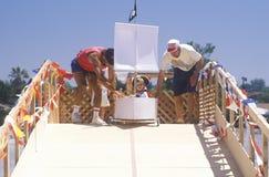 Dos hombres empujan del contendiente joven siguiente en un coche de derby del barco pirata durante la caja anual Derby del jabón  Fotos de archivo