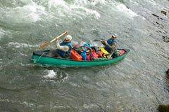 Dos hombres en canoa llena en rápidos salvajes del río Foto de archivo libre de regalías