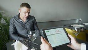 Dos hombres en el café discuten el funcionamiento del negocio almacen de video
