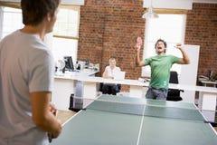 Dos hombres en el espacio de oficina que juega a ping-pong Foto de archivo libre de regalías