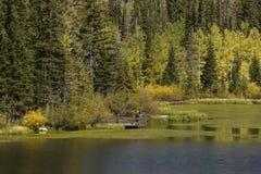 Dos hombres en el lago en otoño Foto de archivo libre de regalías