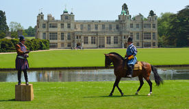 Dos hombres en el traje isabelino uno en un caballo delante del hogar majestuoso Imagen de archivo libre de regalías