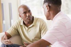 Dos hombres en hablar de la sala de estar Fotografía de archivo libre de regalías