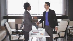 Dos hombres en la oficina después de las negociaciones sacuden las manos