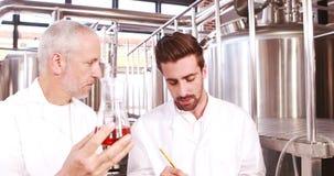 Dos hombres en laboratorio cubren la mirada del cubilete con la cerveza almacen de video