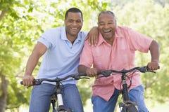 Dos hombres en las bicis al aire libre que sonríen Imágenes de archivo libres de regalías