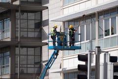 Dos hombres en los cascos que limpian ventanas del edificio alto usando la elevación hidráulica fotografía de archivo libre de regalías