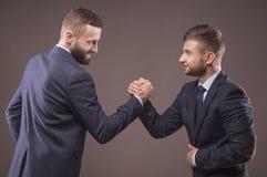 Dos hombres en trajes que luchan en sus brazos Fotos de archivo libres de regalías