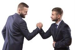 Dos hombres en trajes que luchan en sus brazos Imagen de archivo