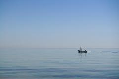 Dos hombres en un barco de motor en el mar Imágenes de archivo libres de regalías