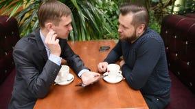 Dos hombres en un café usando un Tablet PC almacen de metraje de vídeo