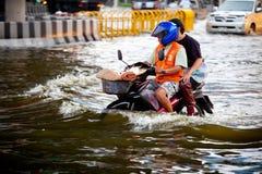 Dos hombres en una moto a través de la inundación Foto de archivo libre de regalías