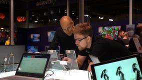 Dos hombres están considerando un ordenador portátil con la pantalla táctil en una tienda de la electrónica metrajes