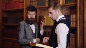 Dos hombres están discutiendo en la biblioteconomía un libro en sus manos Prueba científica en la biblioteca Concepto de almacen de video