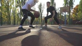 Dos hombres están jugando a baloncesto almacen de metraje de vídeo
