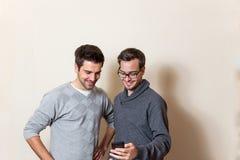 Dos hombres están mirando en un teléfono celular Fotos de archivo libres de regalías
