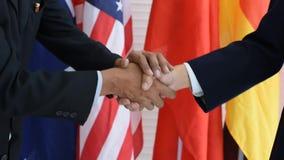 Dos hombres están sacudiendo las manos con el fondo como banderas internacionales
