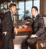 Dos hombres hermosos en smoking en el whisky de la explotación agrícola de la barra Fotos de archivo libres de regalías