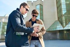 Dos hombres hermosos que usan la tableta al aire libre foto de archivo libre de regalías