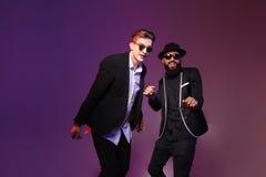Dos hombres jovenes alegres atractivos en el baile de las gafas de sol Fotografía de archivo