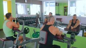 Dos hombres jovenes atléticos que se resuelven en aptitud ejercitan el equipo en el gimnasio metrajes