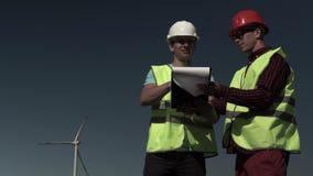 Dos hombres jovenes de los ingenieros se acercan a un molino de viento metrajes