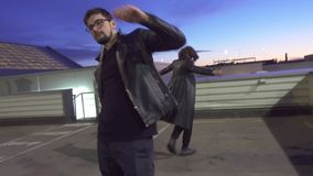 Dos hombres jovenes en chaqueta de cuero negra son de mudanza y de baile en piso afuera almacen de video