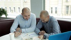 Dos hombres jovenes en el almuerzo en un café de consumición del café y tallarines de la consumición que discuten negocio Trabajo almacen de video