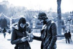 Dos hombres jovenes están mirando smartphones Fotografía de archivo libre de regalías
