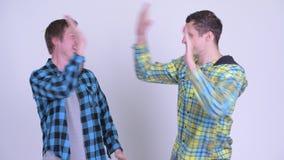 Dos hombres jovenes felices que consiguen buenas noticias juntas almacen de video
