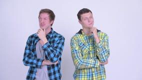 Dos hombres jovenes felices que piensan junto almacen de video