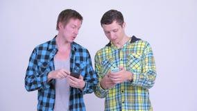 Dos hombres jovenes felices usando el teléfono junto metrajes