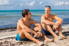 Dos hombres jovenes hermosos que charlan en una playa Fotos de archivo libres de regalías