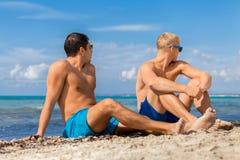 Dos hombres jovenes hermosos que charlan en una playa Imágenes de archivo libres de regalías