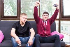 Dos hombres jovenes hermosos que juegan a los videojuegos mientras que se sienta en el sofá Foto de archivo